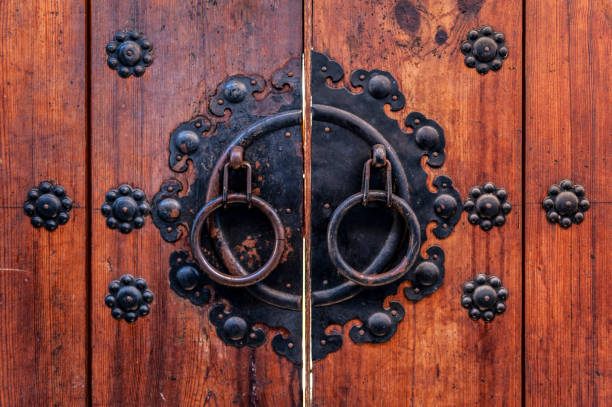 Korean wooden door panels decorated with old black metallic ring handles at a house in ancient village in Jeonju, South Korea stock photo