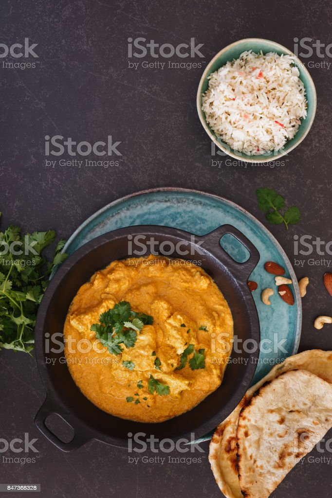 Korma chicken, traditional Indian dish with nuts, jeera rice and naan bread stock photo