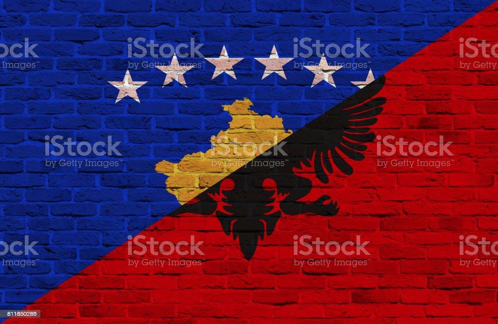 Kosovo and Albanian flag painted over brick wall stock photo