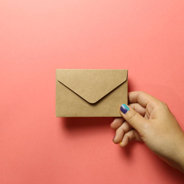 Kraft brown paper envelope with hand on pink background stock photo