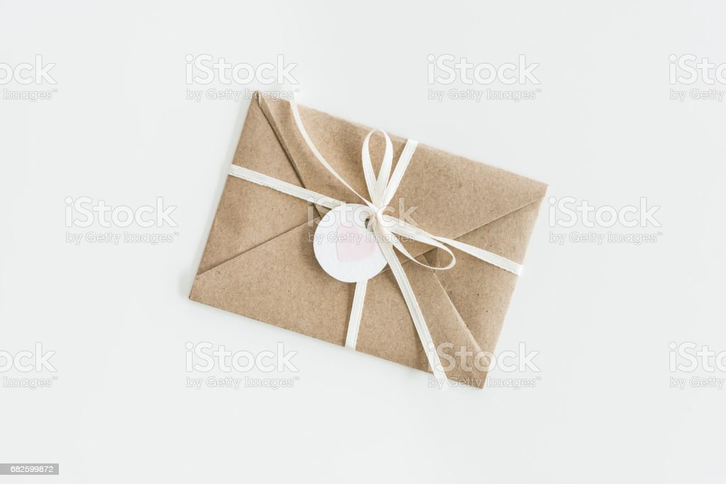 Fotografia De Kraft Envelope With Teg With Heart And Ribbon Isolated