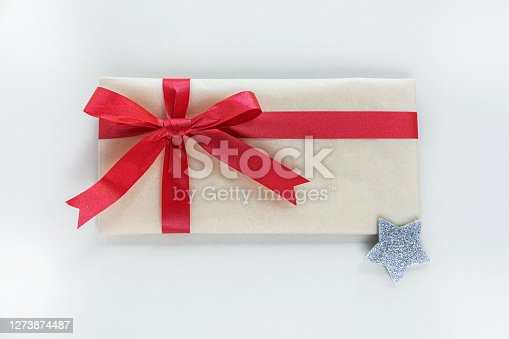 A kraft paper envelope tied with a red festive ribbon is meant to be a gift for Christmas or New Year.