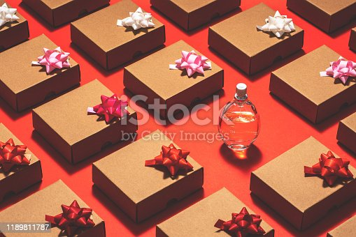 Kraft paper gift boxes with pull bow ribbon flat lay. Perfume bottle on red background.