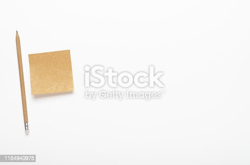 istock Kraft paper sticker with pencil on white background. Office desk, stationery. Copy space, top view, flat lay. 1154940975