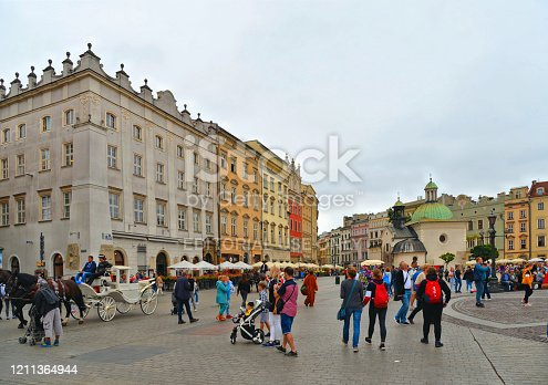 istock Krakow, Poland, rynek glowny. Cityscape with people, Saint Adalbert Church, The Cloth Hall, market square and old buildings in background on summer day. 1211364944
