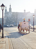 Krakow, Poland. Streets of old town with riding carriage with horses by stone paving stones in time evening sunset. Hazy cityscape in wintertime.