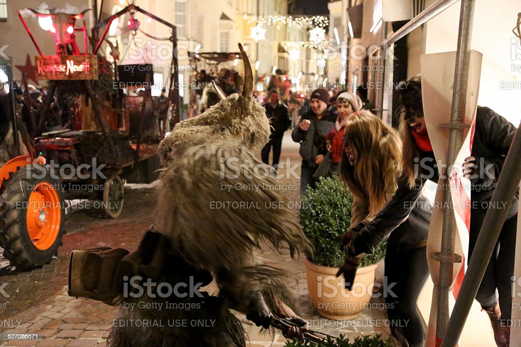 Krampus hitting some girls stock photo
