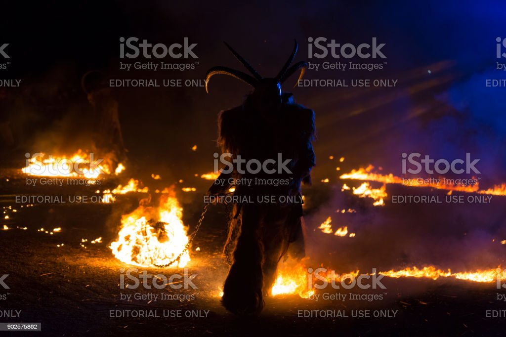 Krampus silhouette dragging fire chain stock photo