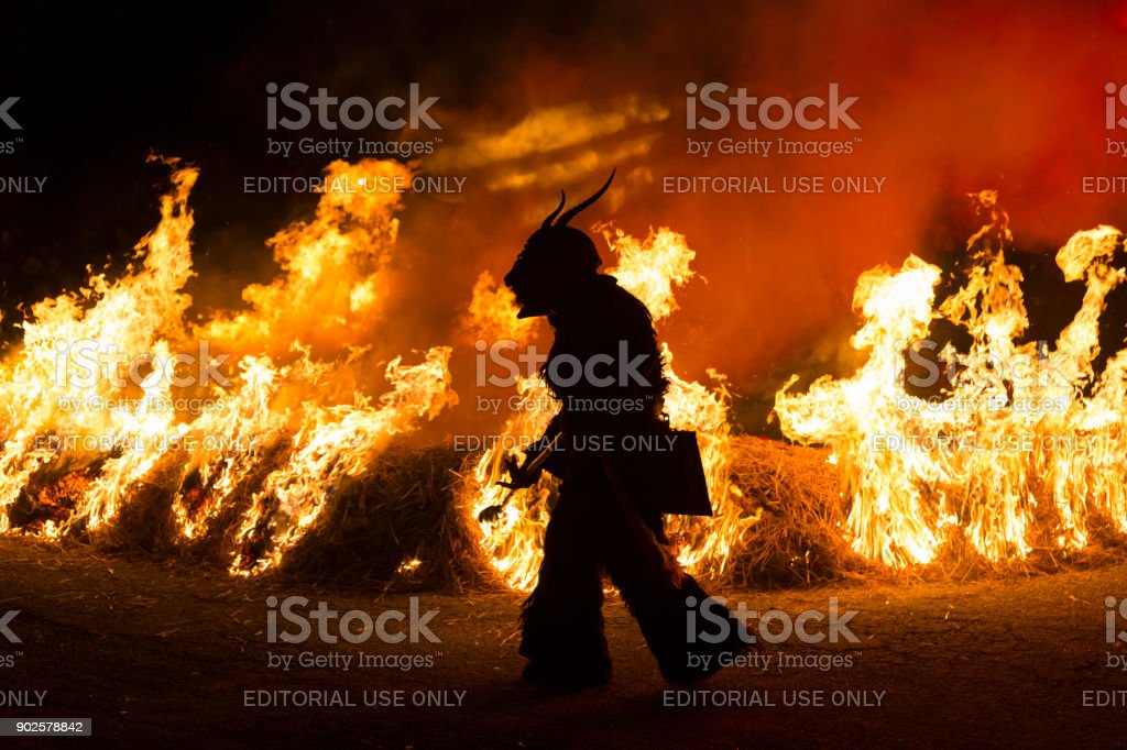 Krampus silhouette walking around fire stock photo