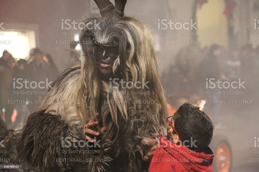 Krampus with a small child stock photo