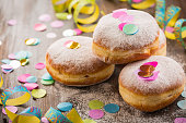 Krapfen, Berliner or  donuts with streamers and confetti. Colorful carnival or birthday image