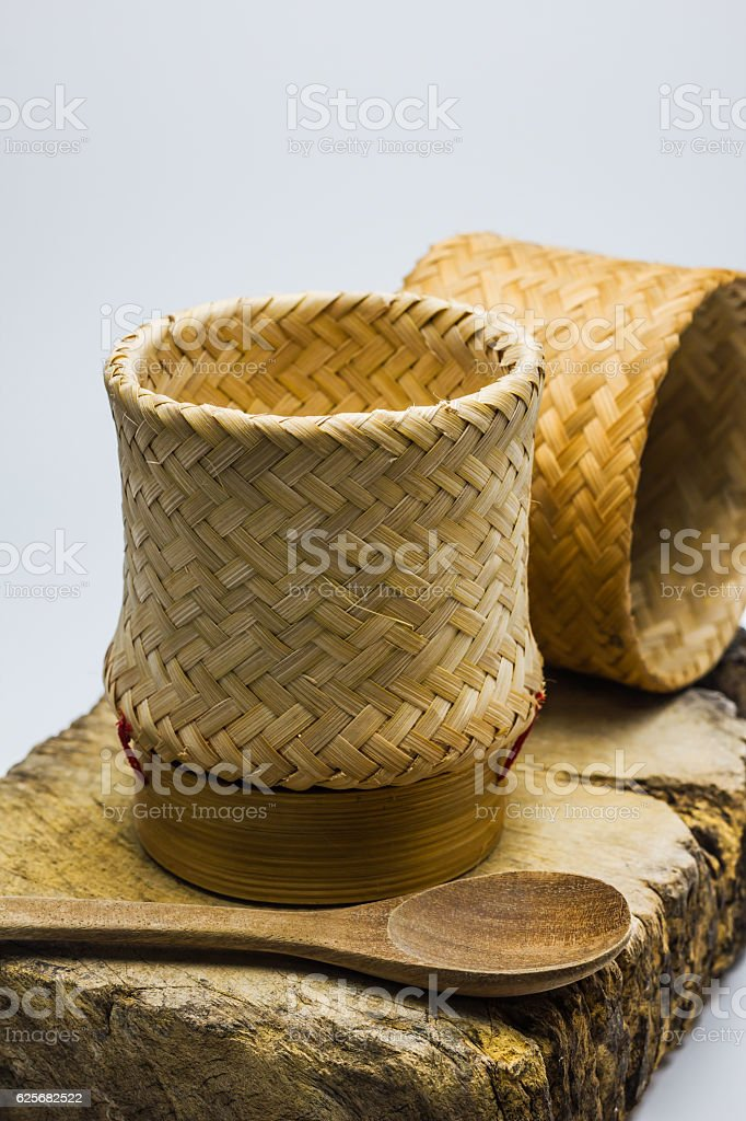 Kratip or Wicker, bamboo container rice on wood block. stock photo