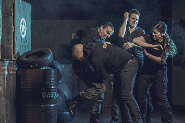 krav maga fighting group training in dark indoor urban setting - punching stock photos and pictures