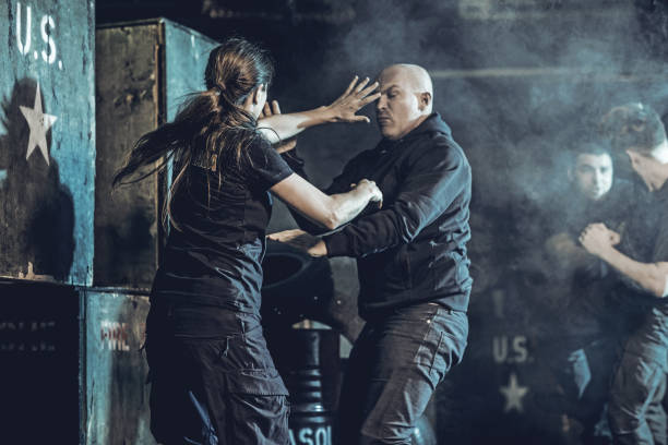 Krav Maga fighting group training in dark indoor urban setting Krav Maga fighting group training in dark indoor urban setting self defense stock pictures, royalty-free photos & images