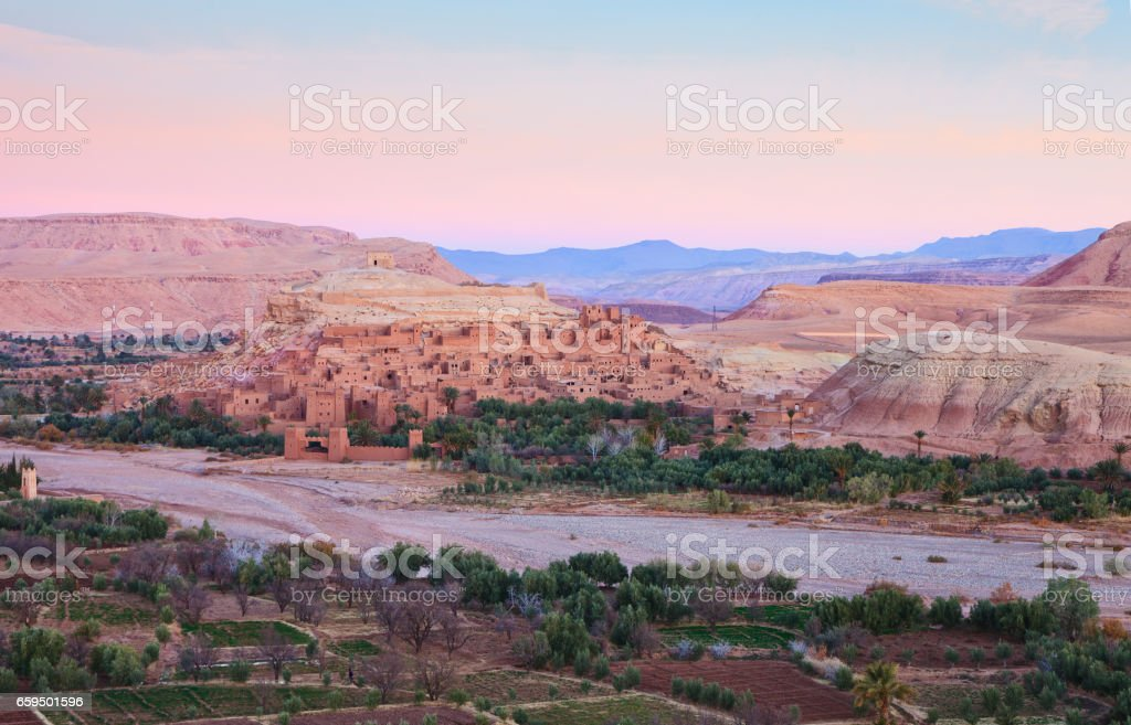 Ksar of Ait-Ben-Haddou and surroundings at dawn, Morocco.    Ait-Ben-Haddou along the bank of a parched river. stock photo