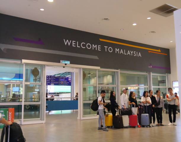 Kuala Lumpur International Airport runway Kuala Lumpur, Malaysia--March 2018: Passengers stand outside a welcome to Malaysia sign at the Kuala Lumpur International Airport or KLIA. kuala lumpur airport stock pictures, royalty-free photos & images