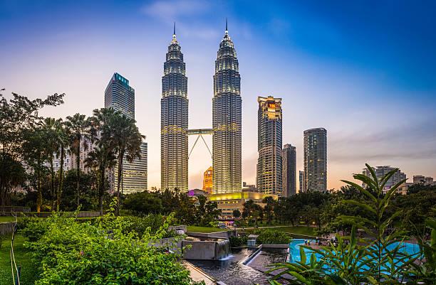 kuala lumpur klcc park petronas towers illuminated at sunset malaysia - maleisië stockfoto's en -beelden