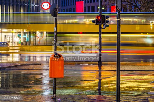 Kudamm in berlin with blurred bus and reflection in wet street by night