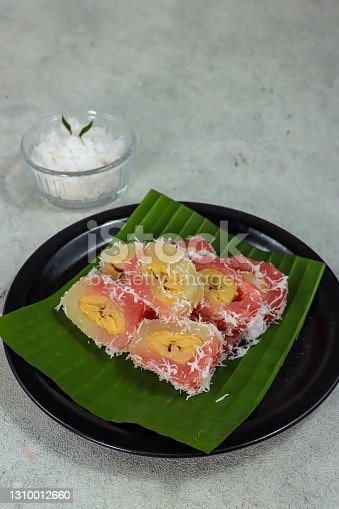 istock Kue mata roda or grubi is Indonesian traditional cake made from cassava, the center of which is filled with bananas, shaped like a wheel, served with grated coconut. 1310012660