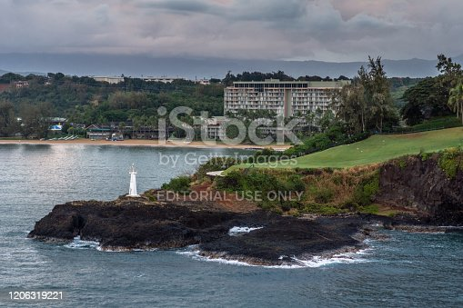 Nawiliwili, Kauai, Hawaii, USA. - January 11, 2012: Early morning light on Kukii Point lighthouse or beacon on black lava rock peninsula with Kalapaki bay and beach and Marriott Beach Resort in back.