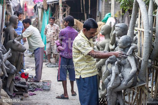 Kolkata, India - February 2, 2015: Unidentified artisans making a Hindu idol from clay in Kumartuli. The place is famous in Kolkata for making various idols of God and Godess for vaious festivals.