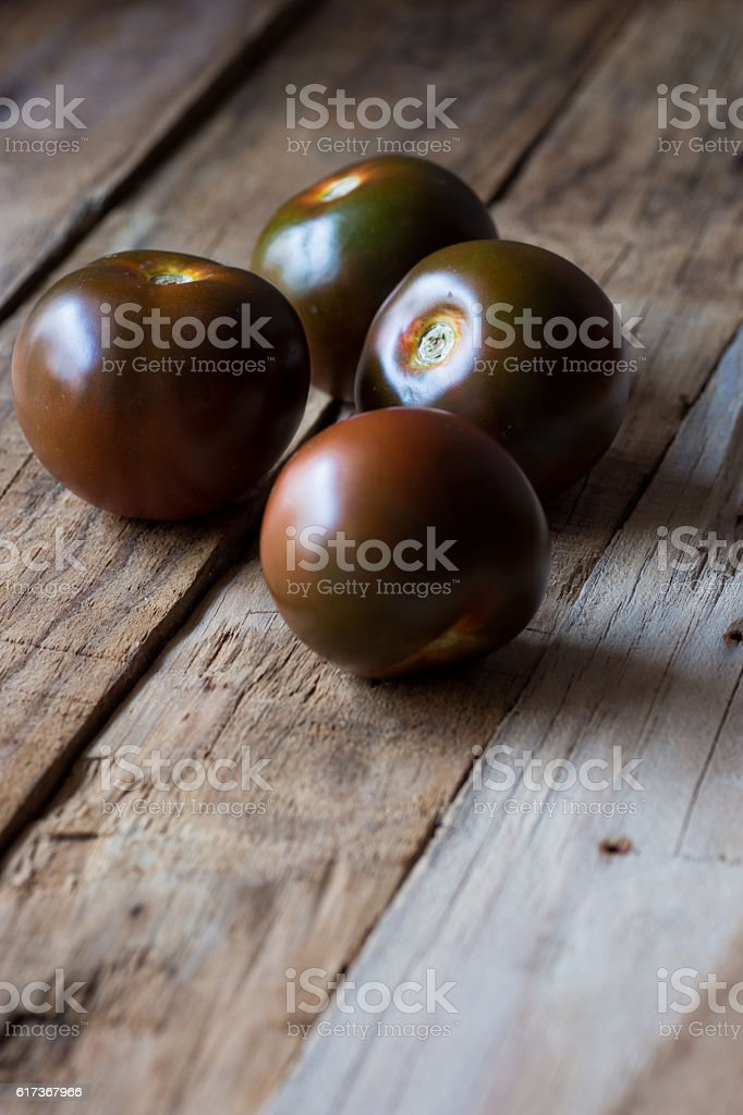 Kumato tomatoes on rustic wood background stock photo