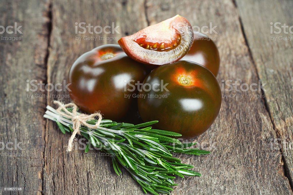 kumato tomatoes on wooden surface stock photo