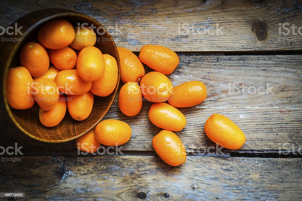Kumquat in a bowl on rustic wooden table stock photo