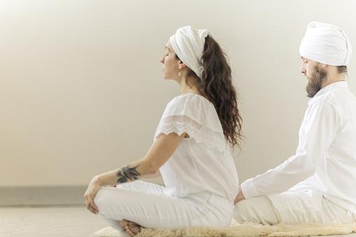 Kundalini. Couple practicing yoga. Lotus pose and meditation