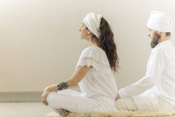 kundalini. paar yoga zu praktizieren. lotus-pose und meditation - kundalini yoga stock-fotos und bilder
