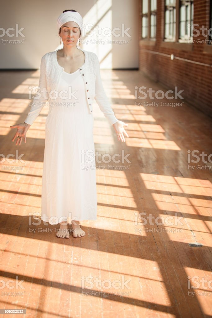 Kundalini. Woman practicing yoga. Standing in the light stock photo