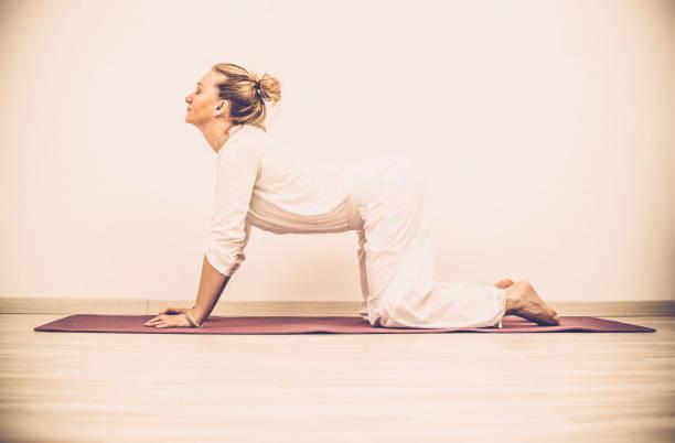 kundalini yoga, kuh-pose, marjarijasana - kundalini yoga stock-fotos und bilder