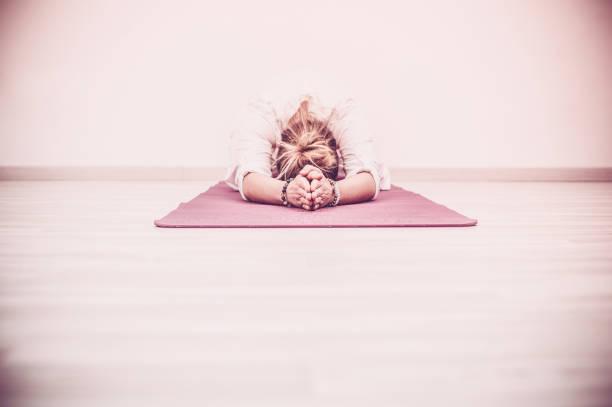 kundalini yoga meditation in baby darstellen, garbhasana - kundalini yoga stock-fotos und bilder