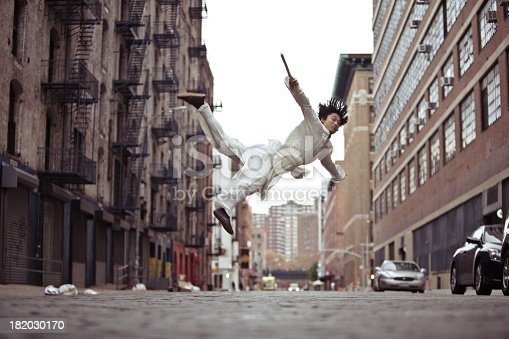 A kung fu martial artist doing a flying roundhouse kick in an alley in New York city