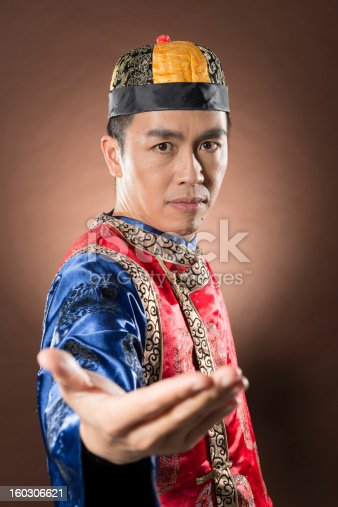 Closeup portrait of Chinese man dress traditional clothes and pose Chinese gong fu attack position.