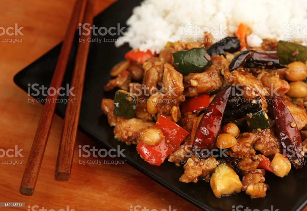 Kung Pao Chicken, white rice, chop sticks on a black plate royalty-free stock photo