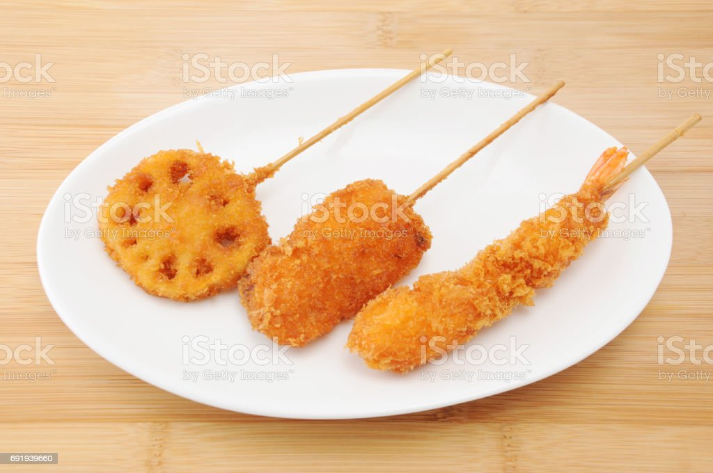 kushikatsu fried vegetable and meat on plate on table cutting board stock photo