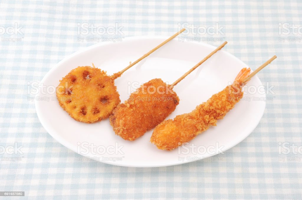 kushikatsu fried vegetable and meat on plate on table stock photo
