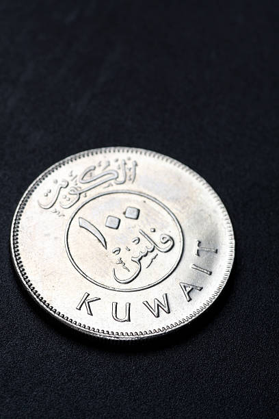 kuwait 100 fils coin in black background - kuwait currency stock photos and pictures