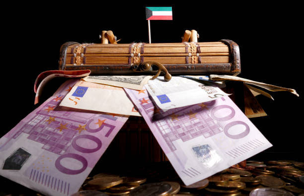 kuwaiti flag on top of crate full of money - kuwait currency stock photos and pictures