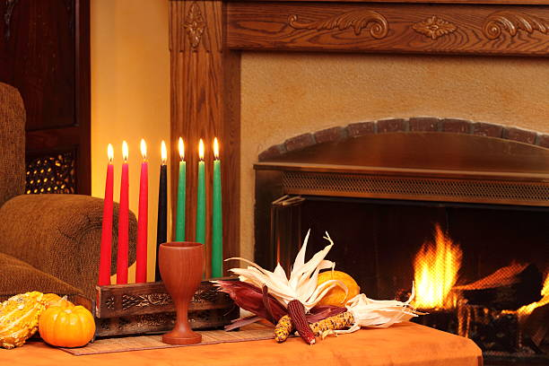 kwanzaa candles by fireplace left horizontal - kwanzaa stock pictures, royalty-free photos & images
