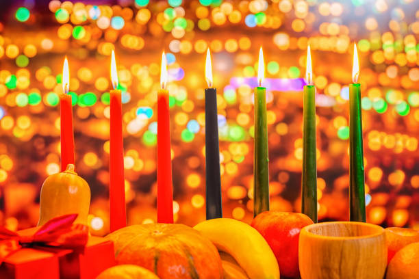 kwanzaa celebration concept with seven candles red, black and green, gift box, pumpkin, bowl and fruit on light blur bokeh background, close up - kwanzaa stock pictures, royalty-free photos & images