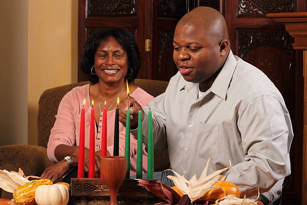 kwanzaa couple horizontal red candles lit - kwanzaa stock pictures, royalty-free photos & images