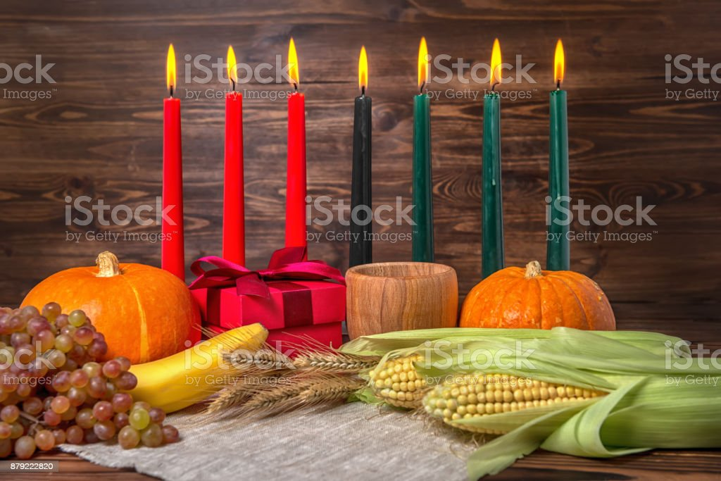 Kwanzaa festival concept with seven candles red, black and green, gift box, pumpkins, ears of wheat, grapes, corns, banana, bowl and fruits on wooden background, close up stock photo