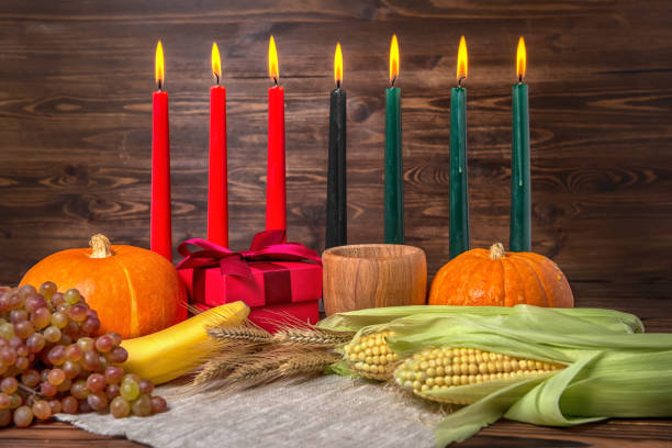 kwanzaa festival concept with seven candles red, black and green, gift box, pumpkins, ears of wheat, grapes, corns, banana, bowl and fruits on wooden background, close up - kwanzaa stock pictures, royalty-free photos & images