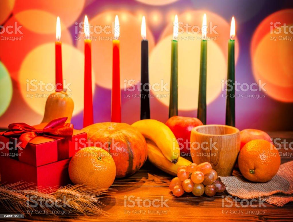 Concepto festivo de Kwanzaa con siete velas rojas, negras y verdes, caja de regalo, calabaza, tazón de fuente y fruto de luz desenfocar fondo bokeh - foto de stock