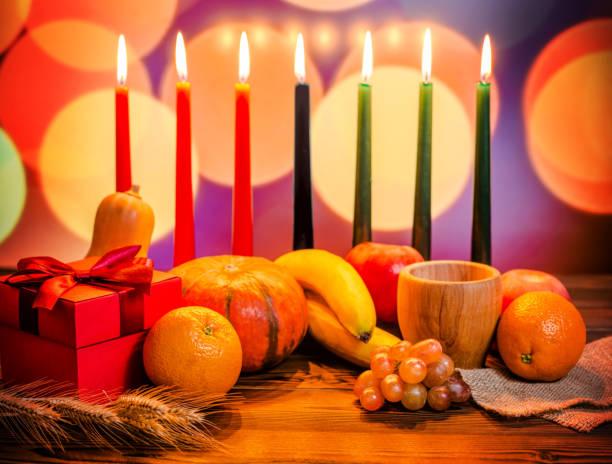 Concept festif de Kwanzaa avec sept bougies rouges, noirs et verts, coffret cadeau, citrouille, bol et fruits sur lumière flou fond de bokeh - Photo