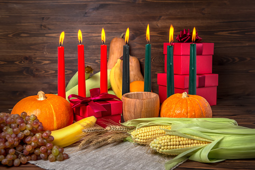 Kwanzaa holiday concept with candles red, black and green, gift box, pumpkins, ears of wheat, grapes, corns, banana, bowl and fruits on wooden background, close up