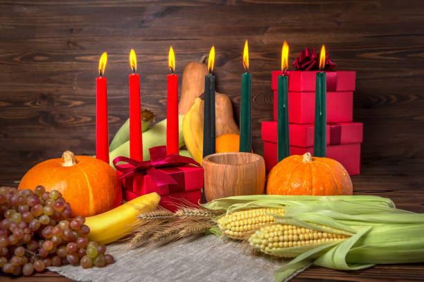 kwanzaa holiday concept with candles red, black and green, gift box, pumpkins, ears of wheat, grapes, corns, banana, bowl and fruits on wooden background, close up - kwanzaa stock pictures, royalty-free photos & images