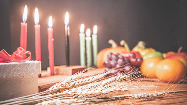 Kwanzaa holiday concept with decorate seven candles red, black and green, gift box, pumpkin,corn and fruit on wooden desk and background. stock photo